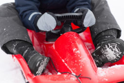 childhood, sledging and season concept - close up of boy driving
